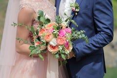 Beau bouquet nuptiale dans des mains de la jeune mariée Bouquet de mariage des roses de pêche par David Austin, aqua tête simple  Image stock