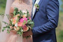 Beau bouquet nuptiale dans des mains de la jeune mariée Bouquet de mariage des roses de pêche par David Austin, aqua tête simple  Photos libres de droits
