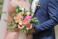 Beau bouquet nuptiale dans des mains de la jeune mariée Bouquet de mariage des roses de pêche par David Austin, aqua tête simple  Photographie stock libre de droits