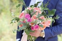 Beau bouquet nuptiale dans des mains du marié Bouquet de mariage des roses de pêche par David Austin, aqua tête simple de rose de Image stock