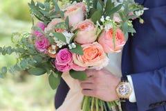 Beau bouquet nuptiale dans des mains du marié Bouquet de mariage des roses de pêche par David Austin, aqua tête simple de rose de Images stock