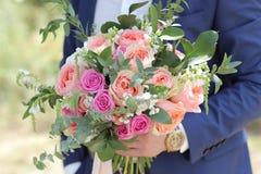 Beau bouquet nuptiale dans des mains du marié Bouquet de mariage des roses de pêche par David Austin, aqua tête simple de rose de Photo stock