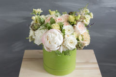 Beau bouquet tendre des fleurs dans la boîte verte sur le fond gris avec l'espace pour le texte Images stock