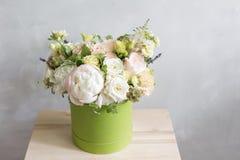 Beau bouquet tendre des fleurs dans la boîte verte sur le fond gris-clair avec l'espace pour le texte Photo libre de droits