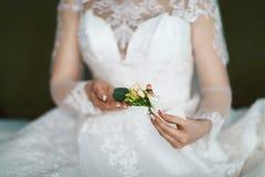 Beau boutonniere sensible de mariage avec les fleurs crémeuses et blanches dans les mains de la jeune mariée dans une robe de den Photo stock