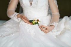 Beau boutonniere sensible de mariage avec les fleurs crémeuses et blanches dans les mains de la jeune mariée dans une robe de den Photographie stock libre de droits