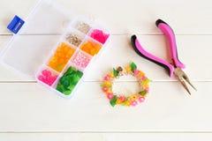 Beau bracelet fait main lumineux pinces Organisateur avec des perles, des fleurs en plastique et des accessoires pour les bijoux  Image stock