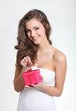 Beau brunette déroulant un cadeau Images libres de droits