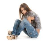 Beau brunette dans la pose de fourrure et de jeans Photographie stock libre de droits