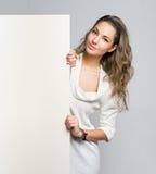 Beau brunette retenant le panneau-réclame vide. photos libres de droits