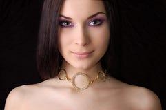 Beau brunette s'usant le collier d'or image stock