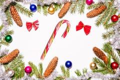 Beau cadre de Noël décoré des jouets et des cônes colorés de branches d'arbre de sapin sur la sucrerie blanche de Noël de fond image libre de droits