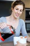 Beau café de portion de jeune femme sur une tasse dans la cuisine à la maison Image libre de droits