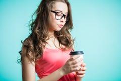 Beau café potable de jeune femme Jeune femme de brune tenant une tasse de papier sur sa main sur un fond bleu photographie stock libre de droits