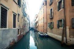 Beau canal à Venise Italie avec des bateaux dans l'eau images stock