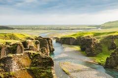 Beau canyon de Fjadrargljufur avec la rivière et les grandes roches Images libres de droits