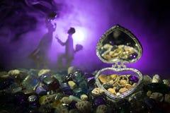 Beau cercueil en forme de coeur ouvert de vieil argent de vintage avec des anneaux de mariage avec la silhouette du jeune homme r Photo libre de droits