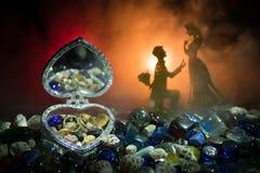 Beau cercueil en forme de coeur ouvert de vieil argent de vintage avec des anneaux de mariage avec la silhouette du jeune homme r Photos stock