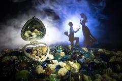 Beau cercueil en forme de coeur ouvert de vieil argent de vintage avec des anneaux de mariage avec la silhouette du jeune homme r Photo stock