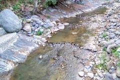 Beau champ avec une petite rivière Terrain montagneux images libres de droits