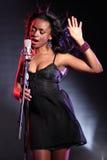 Beau chanteur noir sur l'étape avec le microphone Photos stock
