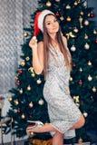 Beau chapeau modèle femelle de Santa d'usage Fille dans une robe près de l'arbre de Noël photographie stock