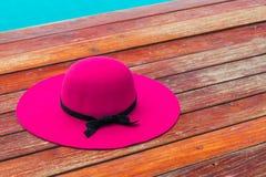 Beau chapeau rose avec l'arc noir sur un plancher en bois par la piscine images libres de droits