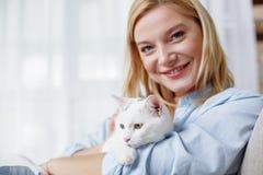 Beau chat d'heureux embrassement de dame à la maison Photographie stock