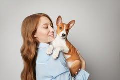 Beau chiot d'une chevelure rouge d'embrassement de fille sur le fond blanc Portrait de studio de la femme attrayante blanche refr photo libre de droits