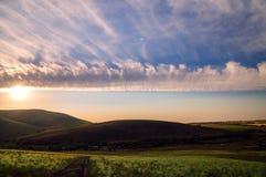 Beau ciel avec des nuages dans la campagne accidentée Image stock