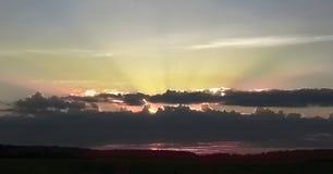 Beau ciel avec l'axe de la lumière du soleil et des nuages pendant le coucher du soleil Image libre de droits