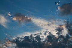 Beau ciel bleu avec les nuages foncés peu communs illuminés par le r Image stock