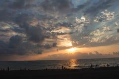 Beau cloudscape au-dessus de la mer, plage du soleil de coucher du soleil Les personnes de silhouettes au fond de coucher du sole Photo libre de droits