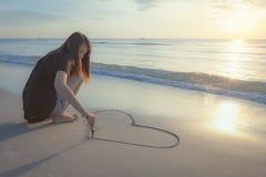 Beau coeur de dessin de femme dans le sable Photos libres de droits