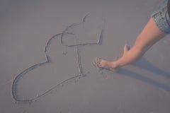 Beau coeur de dessin de femme dans le sable Photo stock