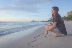 Beau coeur de dessin de femme dans le sable Photographie stock