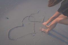Beau coeur de dessin de femme dans le sable Photos stock