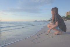 Beau coeur de dessin de femme dans le sable Image stock