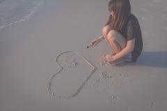 Beau coeur de dessin de femme dans le sable Images stock
