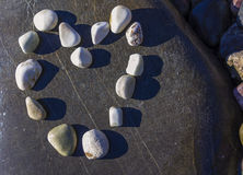 Beau coeur fait de pierres au-dessus de la roche Pierres disposées sous forme de coeur Photographie stock libre de droits