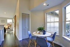 Beau coin-repas avec la table ronde blanche et les chaises bleues photographie stock