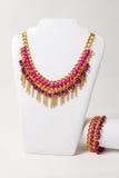 Beau collier rose avec la chaîne d'or et ruban de satin sur un mannequin Photo libre de droits