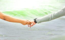 Beau concept, couple heureux tenant des mains sur la mer Images libres de droits