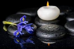 Beau concept de station thermale de fleur de floraison d'iris, de bougies et de pierres noires de zen Photographie stock libre de droits