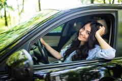 Beau conducteur de femme souriant à vous de sa voiture sur la rue images libres de droits