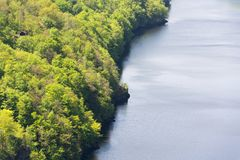 Beau cottage solitaire, chalet caché en bois verts stupéfiants au-dessus des banques de rivière, surface calme de l'eau, paysage  photos libres de droits
