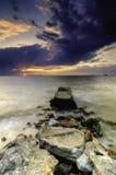 Beau coucher du soleil à la plage avec les nuages mous et foncés dramatiques Photos libres de droits
