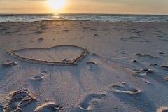Beau coucher du soleil à la plage avec les piles et les dessins en bois de coeurs dans le sable Photos libres de droits