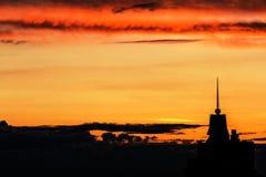 Beau coucher du soleil au-dessus de la ville avec le ciel vif et la construction de beauté Image stock