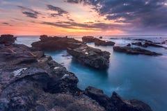 Beau coucher du soleil au-dessus de mer rocheuse de plage de Mengening Image stock